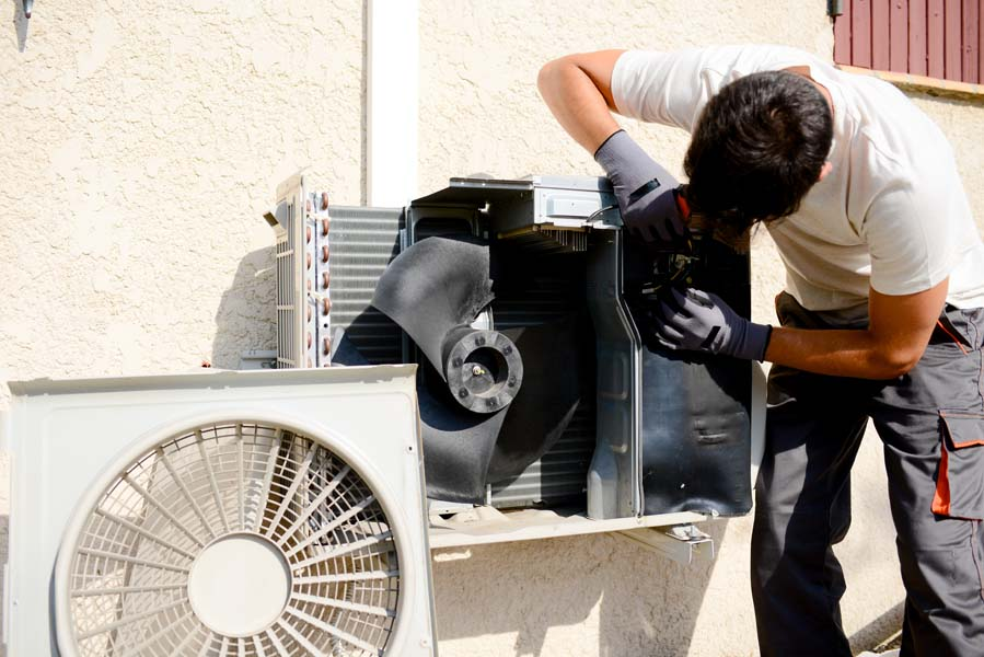 young man electrician installer working on split-system AC at a client's home