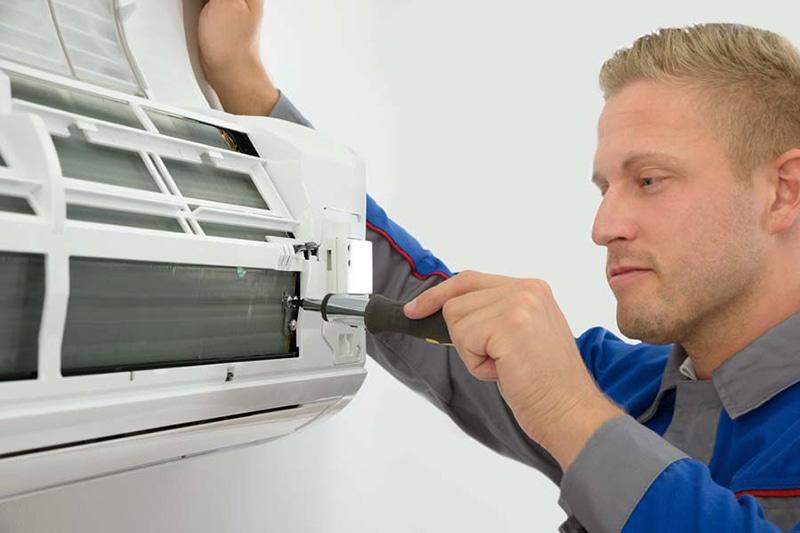 Portrait Of Young Male Technician Repairing Air Conditioner in Birmingham, Alabama