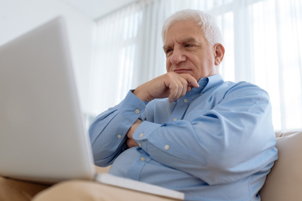 Elderly man sitting on comfy sofa and watching something on laptop, what is that noise coming from my furnace