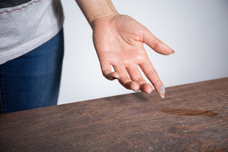 Close-up of dust on woman finger, how to eliminate dust in my home